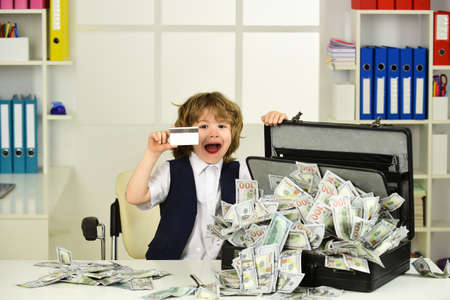 Lottery, win. The child shows a bank card and a suitcase of dollars in cash.