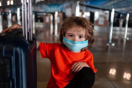 A child with a mask on his face and a suitcase for travel.