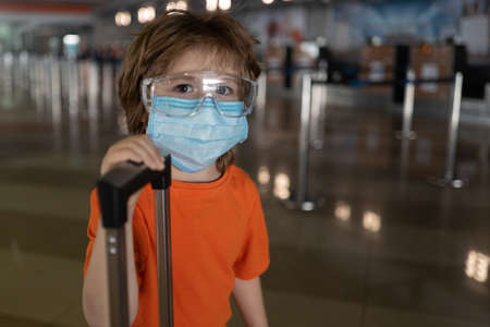 Coronavirus pandemic. A child in a protective mask at the airport.