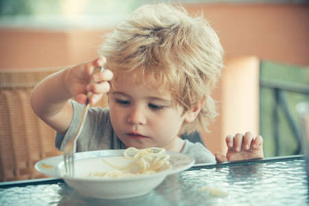 Child and food. Childrens appetite. Baby eating spaghetti. 免版税图像