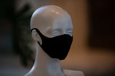 The head of a mannequin in a protective mask during a pandemic. Fashion and business in quarantine.