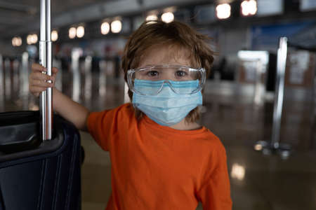 Virus protection and travel. Child face in a mask and glasses. 免版税图像