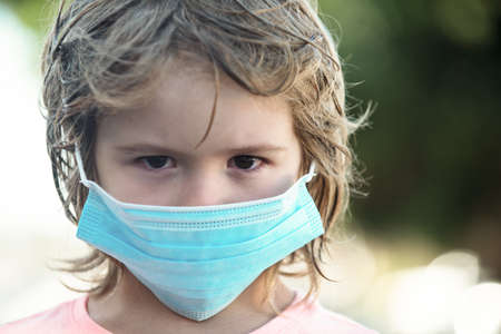A sad child in a mask against virus. Pandemic. 免版税图像
