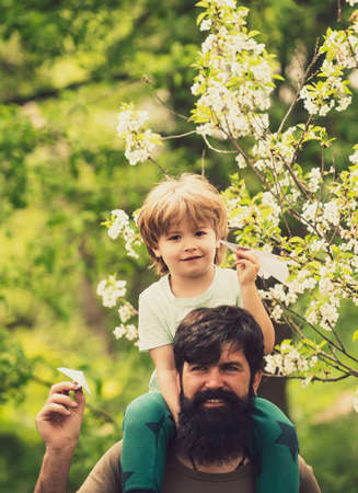 Small boy is sitting on his fathers shoulders. Beautiful spring family concept. Son and dad, friendship. Family walk.