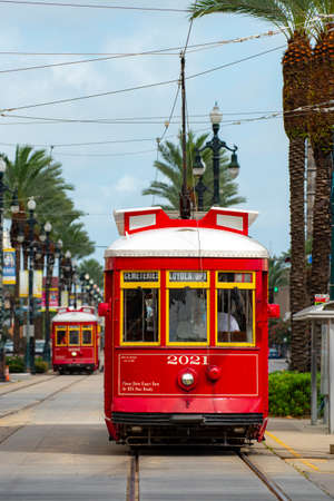 New Orleans, Louisiana, USA - 2020: A historic red streetcar rolls along the train tracks to pick up passengers in New Orleans.