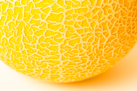 A piece of round yellow melon on a white surface. Texture. Melon skin close up. Shallow DOF, selective soft focus.