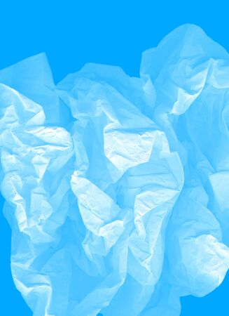 Blue large light elegant cloud of crumpled paper on a cyan background. Airy vertical image. Crushed, creased and wrinkled paper. The concept of lightness, transparency. A modern perfect image for text