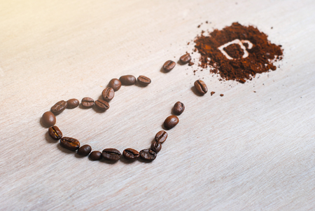 Cup made of coffee beans with heart on the light canvas. I love coffee. Shapes heart and cup made from coffees. Isolated on white background. Coffee cup painted on ground coffee.