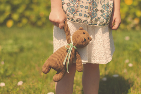 knitted toy in a knitted bag together with a bouquet of wild flowers in the hands of a little girl. Summer walk. Flower meadow.