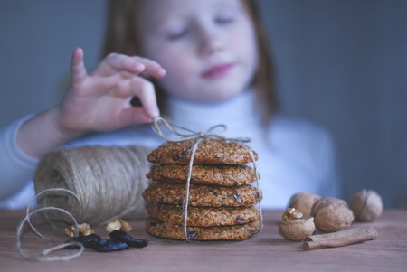 Brown still life, handemade oatmeal cookies, hands near cookies, the girl in the background. Stock Photo