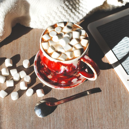 A red cup of cocoa with marshmelow on a gray wooden background with marshmallows and an ebook nearby.