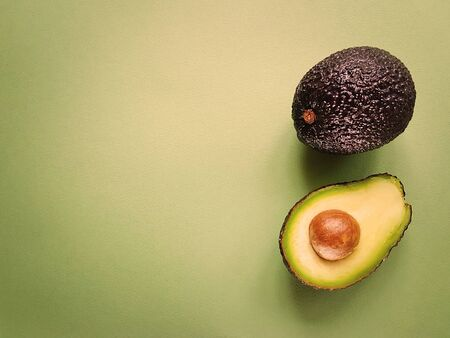 Hass avocado on a green background. Vegan life. Healthy food. Food green.