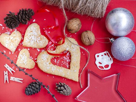 Christmas composition with glass star, biscuits, pine cone, nuts and decorations on a red background. Stock Photo
