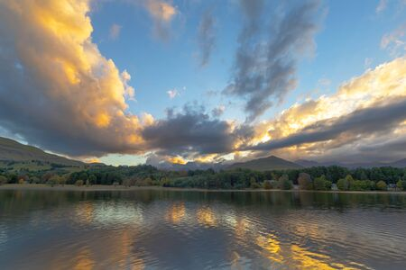 Golden colored clouds at sunset over the lake