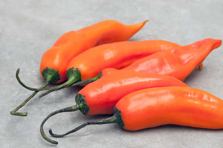 Group of aji amarillo hot chili peppers on stone background