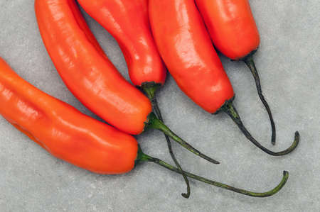 Group of aji amarillo hot chili peppers on stone background from above Stock Photo - 56402519