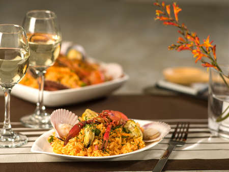 Seafood paella served with wine in fine dining setting