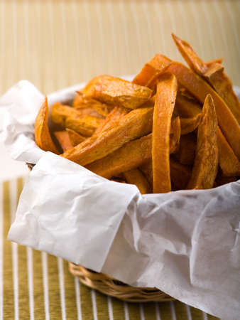 Basket of sweet potatoes fries on textural place mat