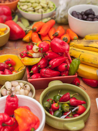 Assortment of Peruvian hot chili peppers in bowls on wooden table top Stock Photo - 56404865