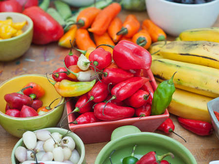Assortment of Peruvian hot chili peppers in bowls on wooden table top Stock Photo - 56404868