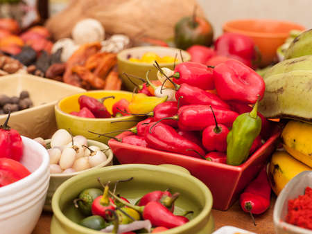 Assortment of Peruvian hot chili peppers in bowls on wooden table top