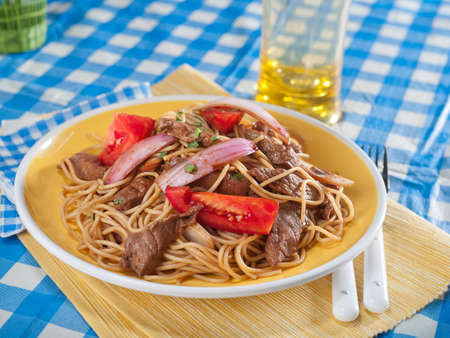 Beef and noodle stir fry, Tallarin saltado, a typical Peruvian dish served in yellow bowl on blue and yellow checked table cloth