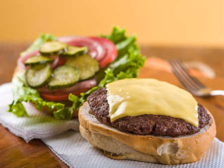 Cheeseburger served open face with lettuce, tomato, pickle and onion garnish sitting on white napkin on wooden table top