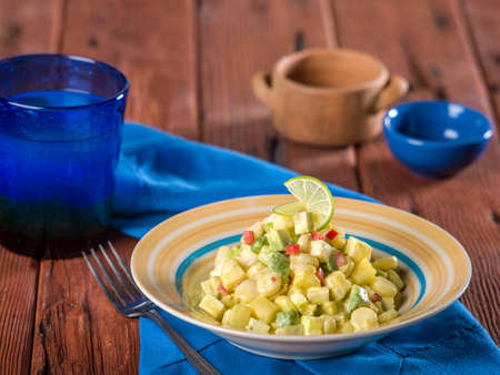 Choclo con queso, a typical Peruvian dish made with corn and cheese served in striped bowl on wooden table top Stock Photo - 56404872