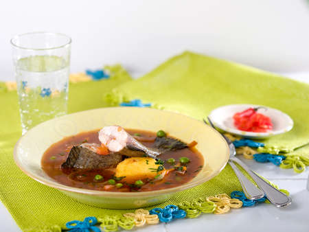 Chupin de pescado, a typical Peruvian fish soup served in yellow bowl on green place mat Stock Photo - 56404874