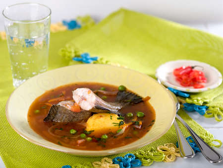 Chupin de pescado, a typical Peruvian fish soup served in yellow bowl on green place mat Stock Photo - 56404875