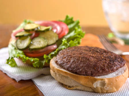 Hamburger served open face with lettuce, tomato, pickle and onion garnish sitting on white napkin on wooden table top