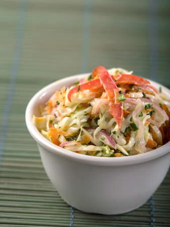 Portion of coleslaw in white dish sitting on green textured place mat