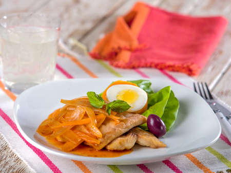Escabeche de pescado, a typical Peruvian fish dish served with pickled onions, olive, and hard boiled egg on white plate sitting on colorful place mat Stock Photo