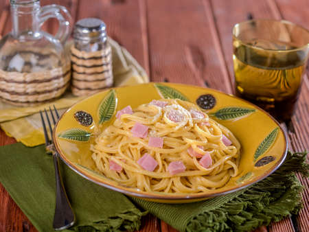 Fettuccine Alfredo with ham served in ceramic dish on wooden table top Stock Photo
