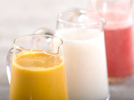 Three pitchers of fresh fruit smoothies closeup on stone table top Stock Photo