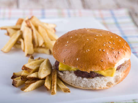 Cheeseburger and french fries sitting on white board on place mat Stock Photo