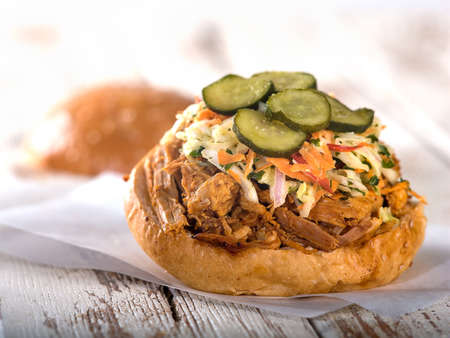 Pulled pork sandwich with coleslaw and pickle garnish sitting on white wooden table top Stock Photo - 56402948