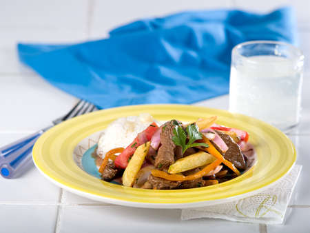 Peruvian beef and onion stir fry, Lomo Saltado, served in yellow dish on white countertop Stock Photo