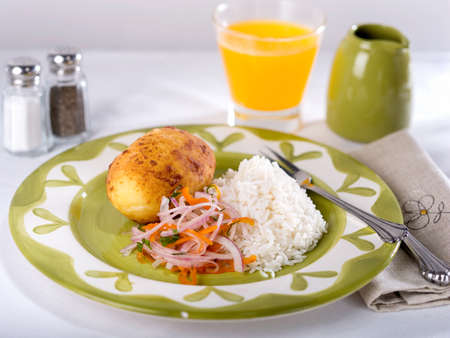 Papa Rellena, a fried potato stuffed with meat servedon white and green plate on white table