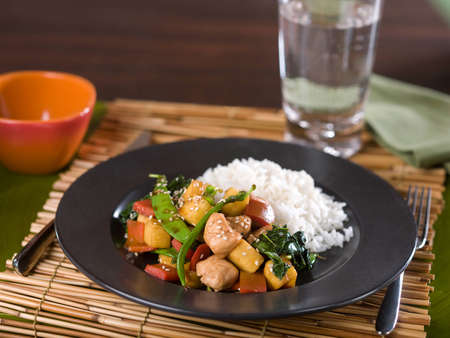 Chinese chicken Teryaki stir fry served on dark ceramic plate with fork and knife on bamboo place mat