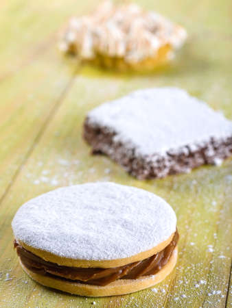 Alfajor cookie, a typical Peruvian dessert served on light green wooden table top Stock Photo