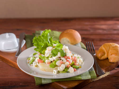 Solterito, a corn and lima bean salad, a typical Peruvian dish served on white plate on wooden table top