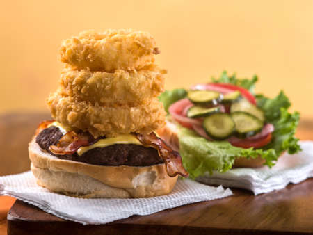 Bacon cheeseburger with stack of onion rings sitting on paper napkin on wooden table top
