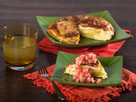 Portion of Spanish omelet on green plate served on wooden table top Stock Photo