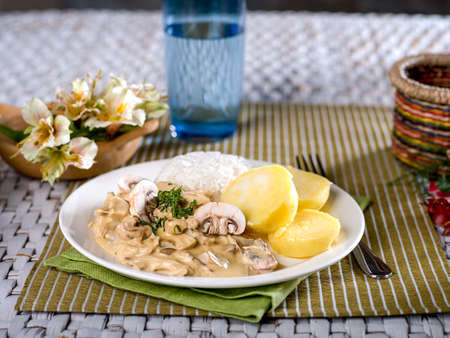 Chicken a La King with rice and potatoes served on white plate on textural place mat