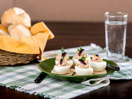 Stuffed eggs with pate on green plate with plaid place mat on wooden table top