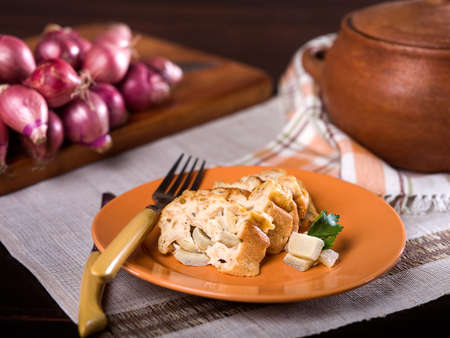 Artichoke bread pudding, Budin de alcachofas, a typical Peruvian dish served on orange plate on textural place mat