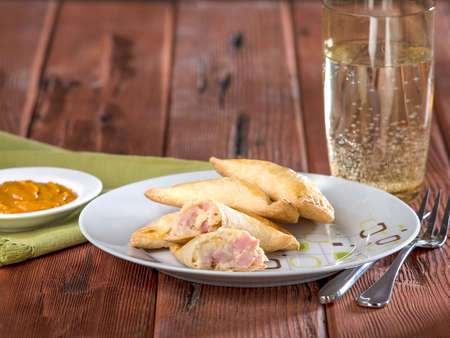 Ham and cheese epmanadas, empanadas mixtas, a typical Peruvian dish served on white plate on wooden table top Stock Photo - 56445038