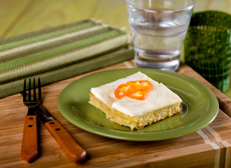 Cornbread, pastel de choclo, a typical Peruvian dish served on green plate on wooden cutting board Stock Photo