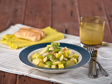 Butter bean salad, Pallares guisados, a typical Peruvian dish served in blue and white dish on wooden table top Stock Photo